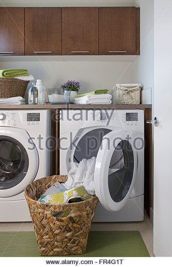 Contemporary laundry room with basket of clean clothes. - Stock-Bilder