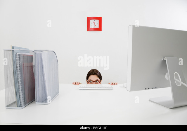 Young businesswoman hiding behind desk Copy space - Stock Image