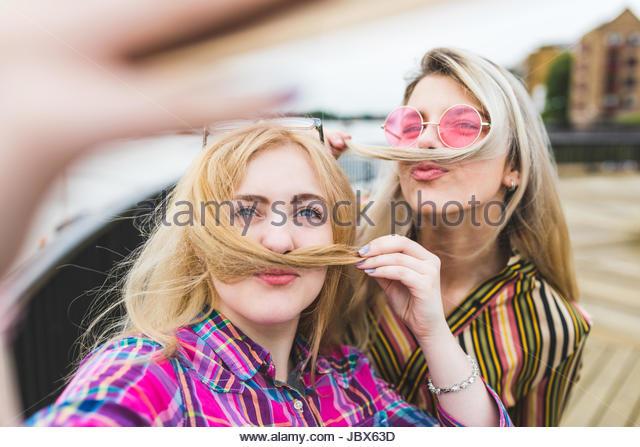 Two female friends, outdoors, taking selfie, pulling hair across lip to make moustache - Stock-Bilder