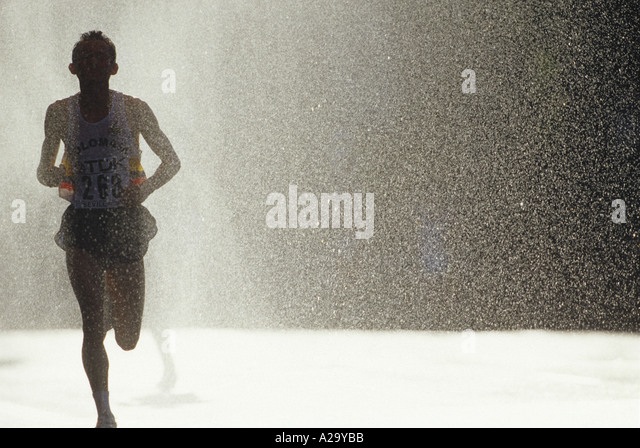 A male runner passes through a cooling water spray during a marathon race - Stock Image