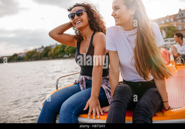Outdoors shot of two female friends sitting in front pedal boat. Teenage friends relaxing on pedal boat in lake - Stock Image