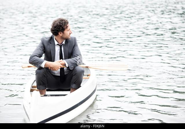 Germany, Rur Reservoir, businessman relaxing in canoe - Stock Image