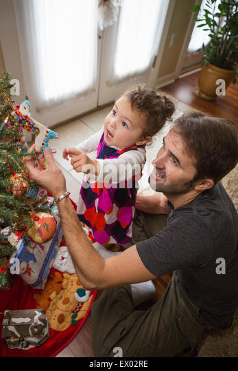 Father and daughter placing Christmas ornaments on tree - Stock Image
