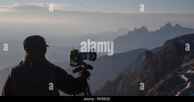 Photographer shooting on the slopes of Tre Cime, Dolomite Mountains,  Belluno Province, Veneto, Italy - Stock Image