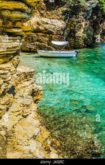 White boat in small cute azure bay surrounded by lime stone cliffs in Corfu island, Greece - Stock Image