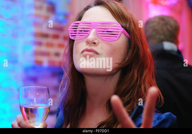 Portrait Of Young Woman Wearing Pink Eyeglasses Gesturing Peace Sign - Stock-Bilder