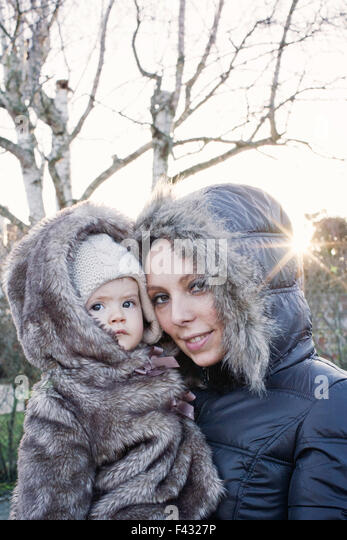 Mother holding baby girl outdoors, both wearing winter coats, portrait - Stock Image