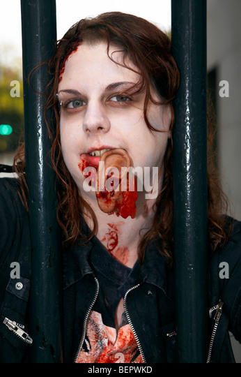 People dressed as Zombies talk along Oxford street London. Part of world Zombie day - Stock Image