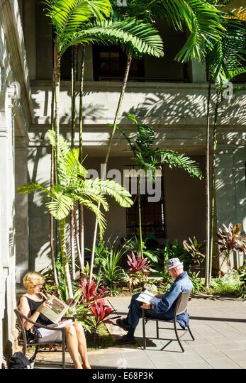 Hawaii Hawaiian Honolulu Hawaii State Library courtyard man senior woman reading sitting - Stock Image