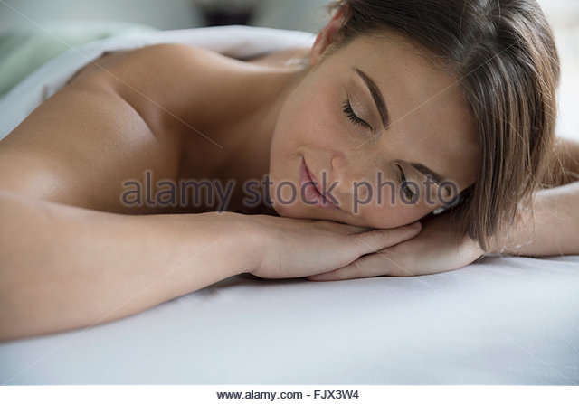 Serene woman laying massage table with eyes closed - Stock Image