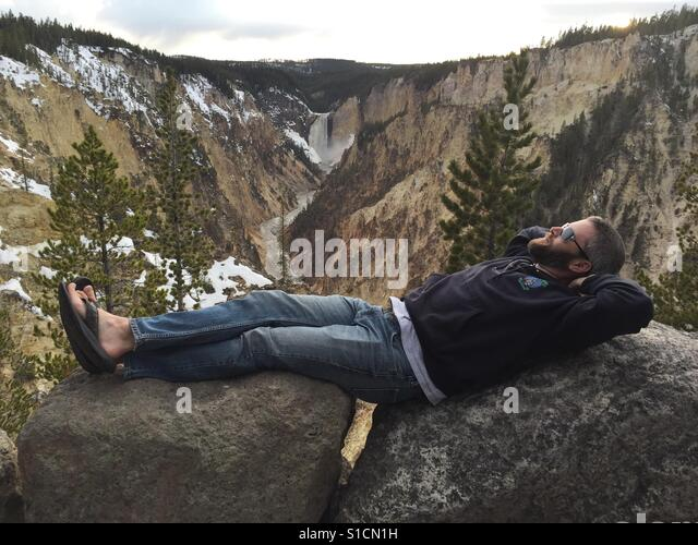 A man reclines across boulders with Upper Falls at Yellowstone National Park in the background. - Stock-Bilder