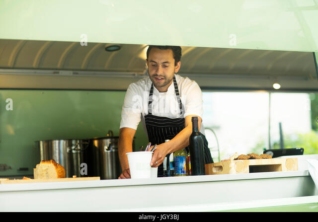 Small business owner preparing food in van food stall - Stock Image