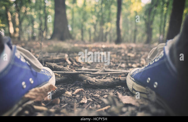 Man in sneakers in the forest - Stock Image