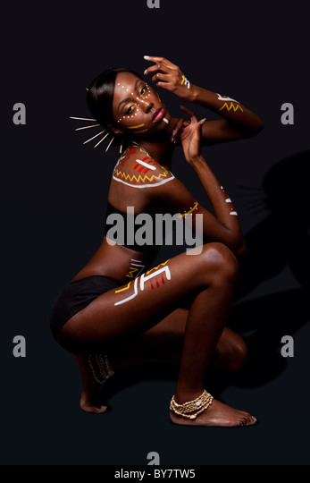 exotic African female fashion with tribal yellow red and white makeup cosmetics and sticks in hair, in cultural - Stock Image