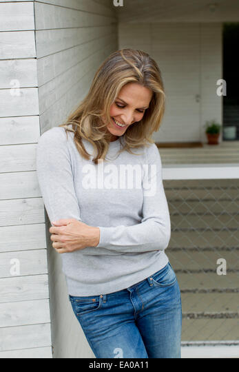 Mature woman with arms folded, smiling - Stock Image