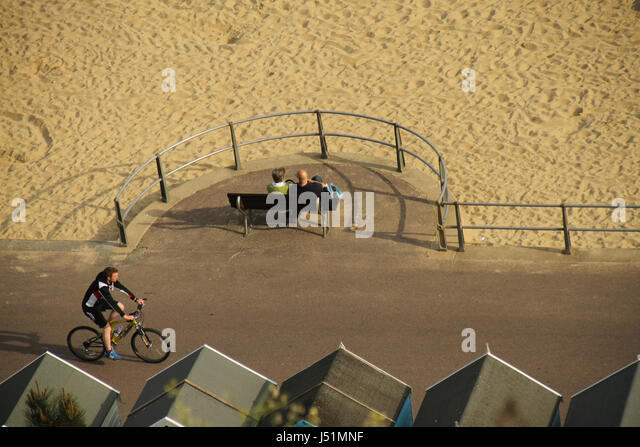 Bournemouth, UK -  11 May: A cylcist rides along the Bournmouth sandy beach. General view of the seaside town of - Stock Image