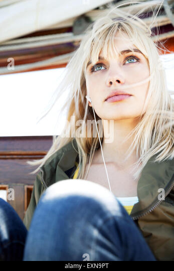 Young woman on a sailing ship listening to music - Stock-Bilder