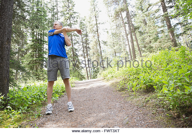 Middle-aged man stretching outdoors - Stock Image
