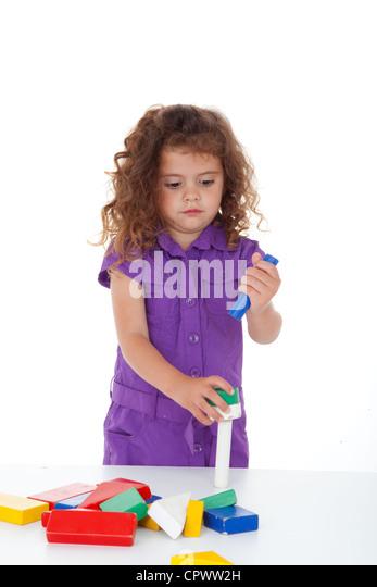 kindergarten child playing with building bricks or blocks - Stock Image