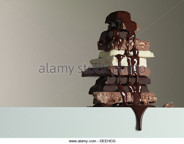 Chocolate syrup dripping over stack of chocolate bars - Stock Image