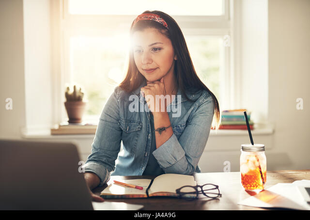 Young female entrepreneur sitting and browsing computer at the workplace in office. - Stock Image