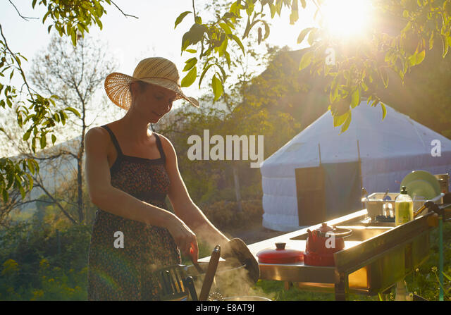 Young woman cooking food whilst glamping, Sierra Nevada, Andalucia Granada, Spain - Stock Image