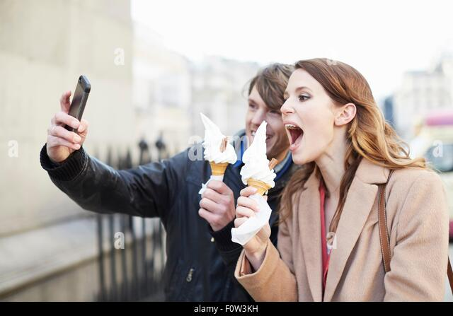 Couple with ice cream cones taking smartphone selfie, London, UK - Stock Image