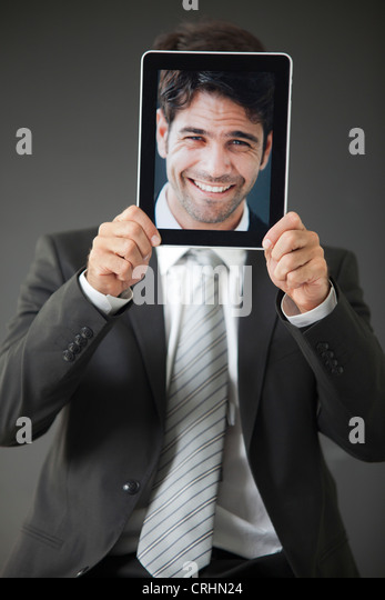 Man holding smiling photograph in front of his face - Stock Image