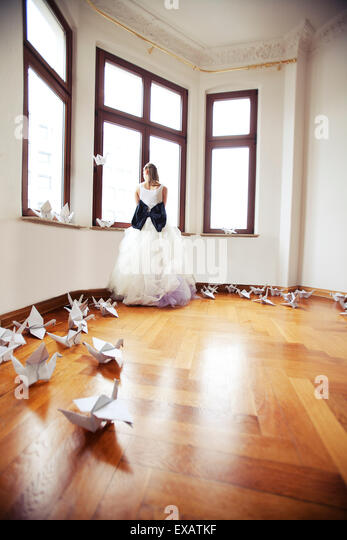 Bride stands in an empty flat in an old building, looks from the window - Stock-Bilder