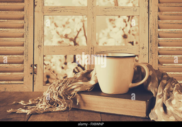 romantic scene of cup of coffee next to old book in front of countryside view outside of the old rustic window. - Stock Image