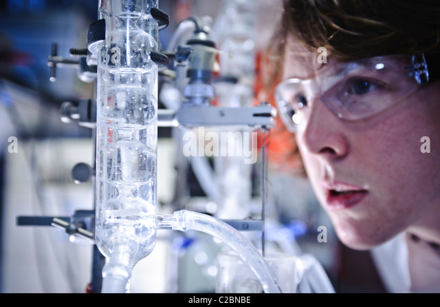 Young male scientist wearing goggles looking intensely at clear liquid swirling in large glass tube in science laboratory - Stock Image