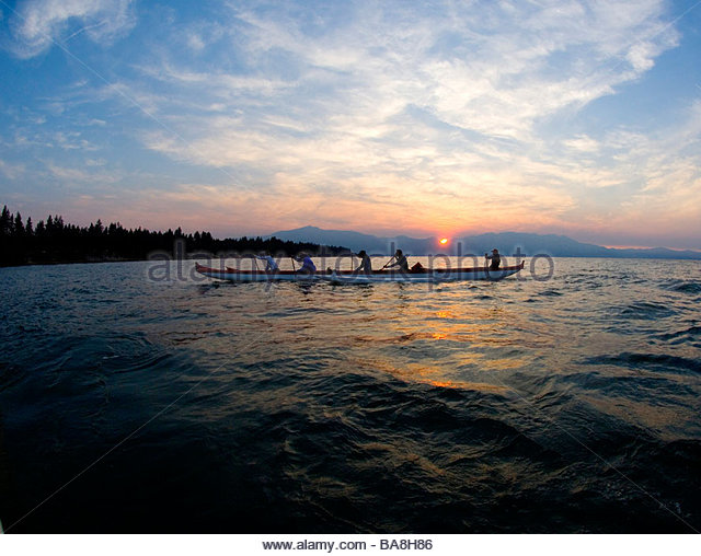 Five People Paddling a Outrigger Canoe on Lake Tahoe at Sunset, California - Stock Image