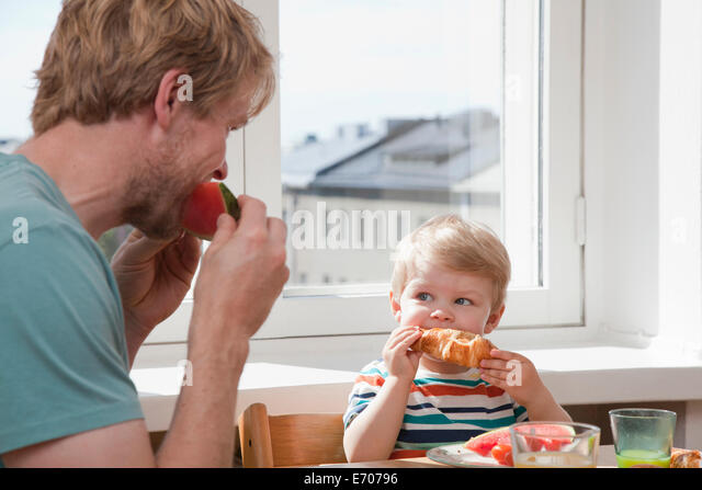 Father and toddler son eating breakfast at kitchen table - Stock Image