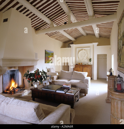 Sitting room with matching sofas, lit fire and beamed ceiling - Stock Image