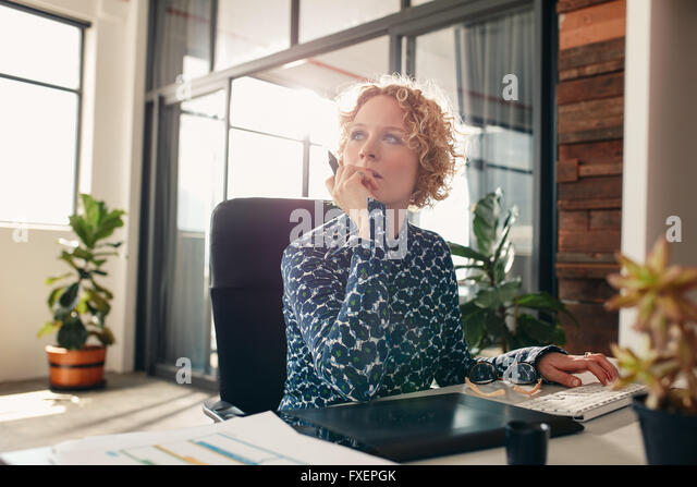 Portrait of young female designer sitting at her desk looking away and thinking. - Stock Image
