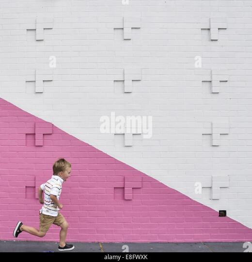 Boy running past pink and white wall - Stock-Bilder