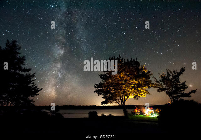 Friends sitting at campfire and milky way, Malay Falls, Nova Scotia, Canada - Stock Image