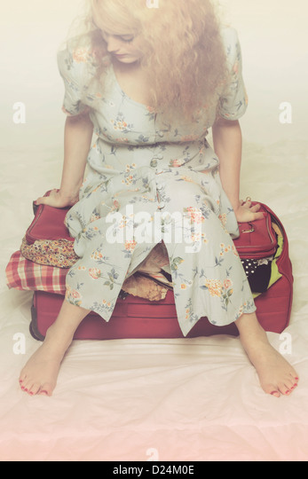 a woman tries to close a suitcase by sitting on it - Stock Image