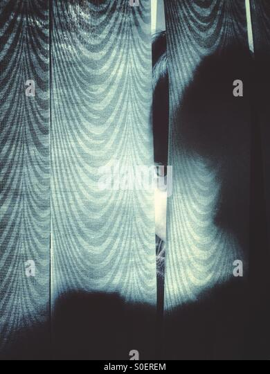 Scared little boy hiding behind the curtains - Stock Image
