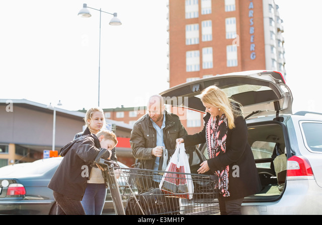 Family loading groceries in car trunk at parking lot - Stock-Bilder