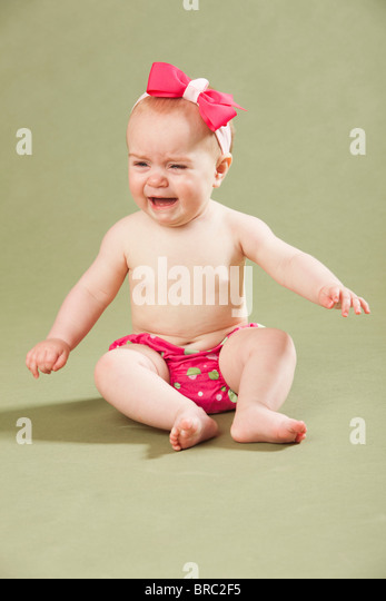 Baby Girl Wearing A Bow In Her Hair And Crying - Stock Image