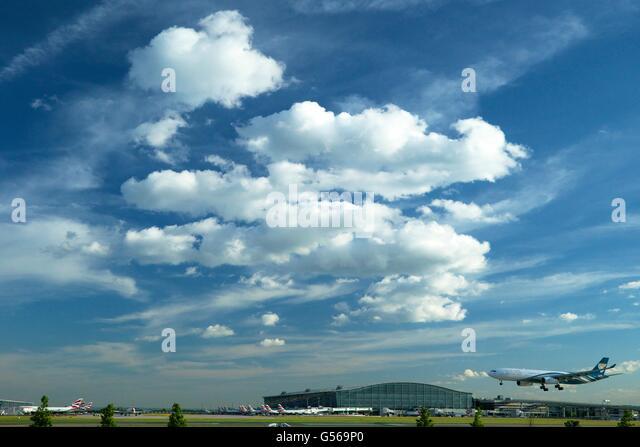 Oman Air flight landing at Heathrow Airport with Terminal 5 behind, London, England, UK, GB, - Stock Image