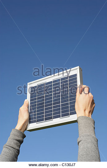 detail of woman holding solar panel up against sky - Stock Image