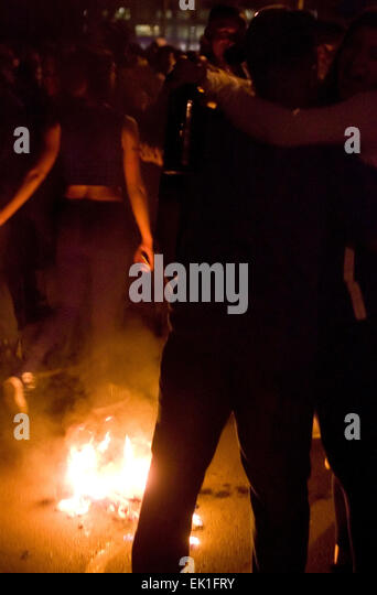 Wisconsin, USA. 05th Apr, 2015. A young woman and man embrace while standing by a pile of burning debris on State - Stock Image