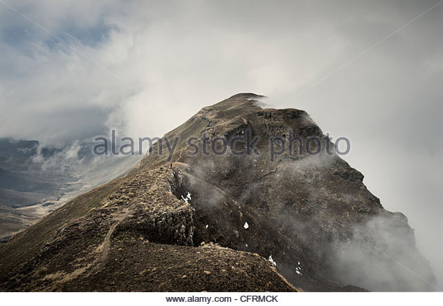 Hiker descending from Cathedral Peak, Drakensberg, South Africa. - Stock Image