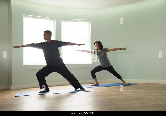 Front view of mature couple in warrior pose looking away - Stock Image