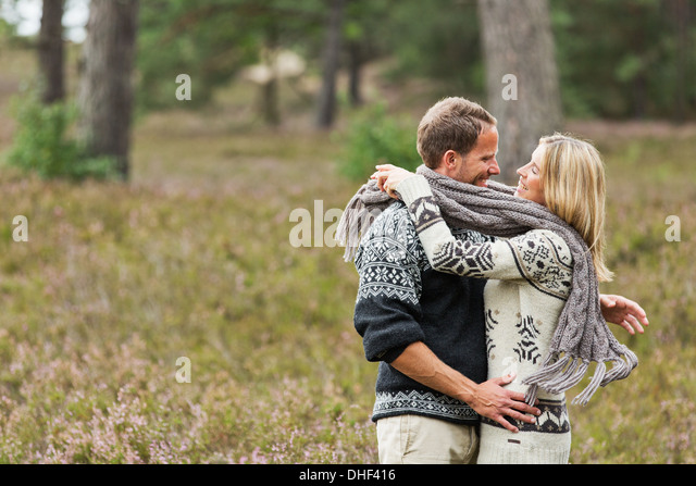 Mid adult couple wrapped in scarf hugging - Stock Image