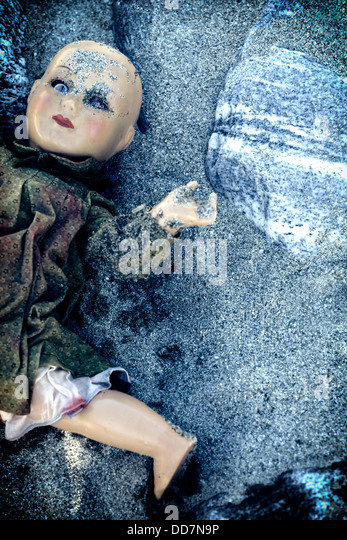 a broken doll, half buried in sand - Stock Image