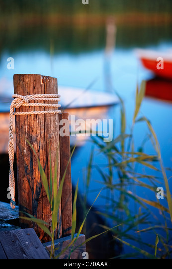 Rope tied on wooden post at dock - Stock Image