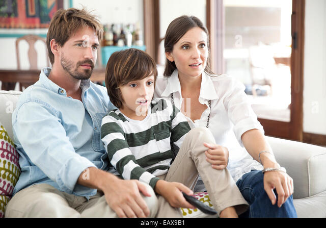 Family watching TV together - Stock-Bilder